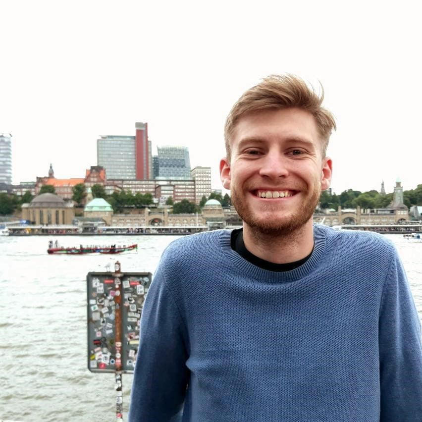 Smiling blonde man in a blue jumper standing in front of a river in a city