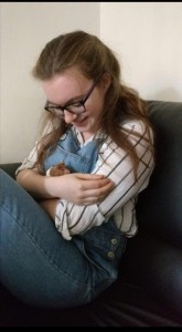 Young woman with long light brown hair wearing denim dungarees holding a hamster and looking at it