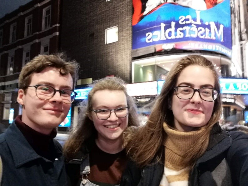"Two young brown haired women and a brown haired boy in glasses outside a theatre with the sign ""Les Miserables"""